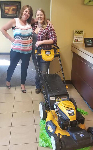 1st-time Home Buyer Keely pictured with the new lawnmower she and Quinten received from 1st CCU and Molli Hundt, Mortgage Loan Officer