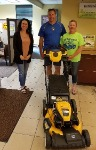Jason and Carrie, first time home buyers, pictured with Mortgage Lender Lisa Miller and their new free lawnmower