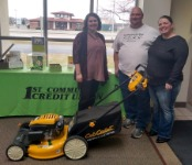 Liza Schlintz pictured with first-time home buyers and their new free lawnmower