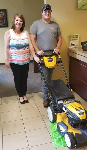 1st-time homebuyer Andrew, pictured with Mortgage Loan Officer Molli Hundt and his new lawnmower, courtesy of 1st CCU