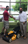 1st-Time home buyer Ben pictured with his new lawnmower and Michael Garcia, Mortgage Loan Officer