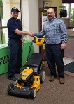 1st-Time Home Buyer Tyler, pictured with his new lawnmower and Michael Garcia, Mortgage Loan Officer
