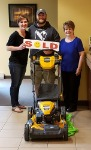 First-time home buyer Bruce, pictured with his new lawnmower, his realtor Diane McNulty, and Barb Burnham, Mortgage Loan Officer.